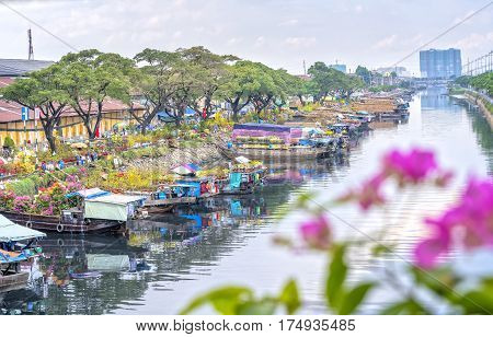 Ho Chi Minh City, Vietnam - January 26, 2017: Flowers boats at flower market on along canal wharf. This is place where farmers sell apricot blossom and other flowers on Lunar New Year in Vietnam