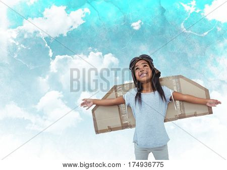 Digital composite image of smiling girl pretending to be a pilot against cloudy sky background