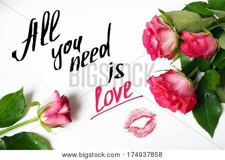 Valentines day background with pink roses imprint of lipstick and text