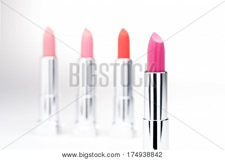 Close-up view of glamorous lipstick with set of fashionable lipsticks behind