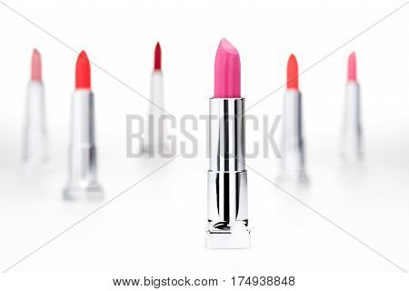 Close-up view of fashionable glossy lipstick with set of different lipsticks behind