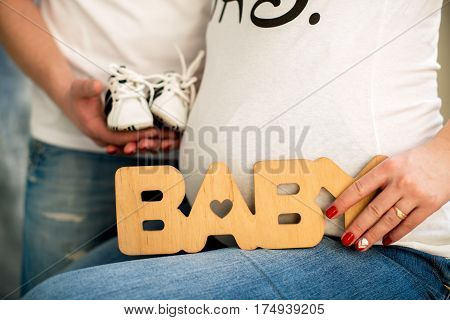 Cropped image of pregnancy woman and her husband holding baby shoes and hugging the tummy. A pregnant woman is holding a wooden sign baby