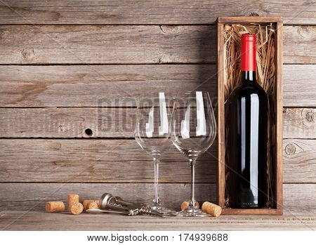 Red wine bottle in box and glasses in front of wooden wall. With copy space