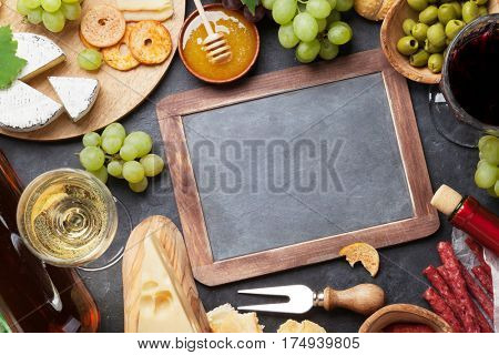 Red and white wine, grape, cheese and sausages over stone table. Top view with blackboard for copy space
