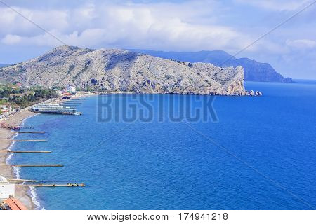 Background blurred landscape view from above to the Sudak Gulf, Cape Alchak and the city of Sudak and its embankment in the Crimea