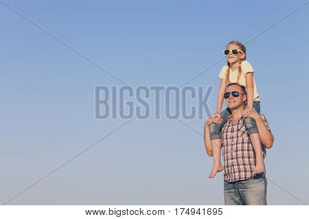 Dad And Daughter In Sunglasses Playing In The Park At The Day Time.