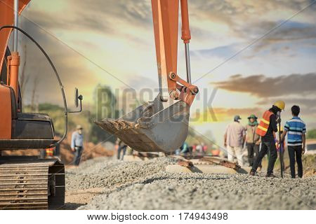 Back hoe and blurred construction worker in safety uniform in railway constructionconstruction site background