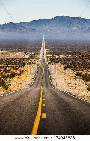 Classic vertical view of an endless straight road running through the barren scenery of famous Death Valley with extreme heat haze on a beautiful sunny day with blue sky in summer California USA