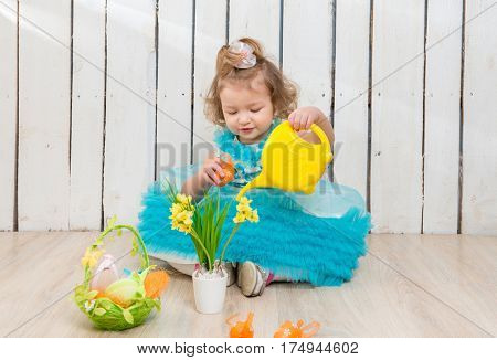 cute little girl watering flowers in pot on the floor
