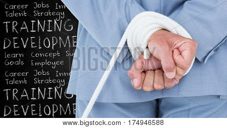 Digital composite image of a businessman with hands tied and training and development concept against black board