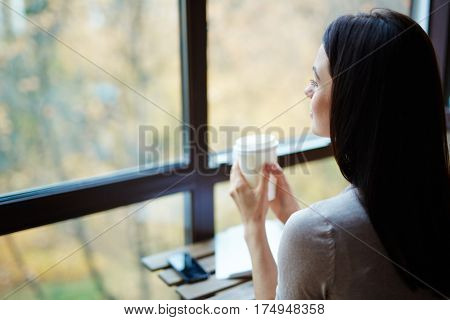 Adolescent female with drink looking through window