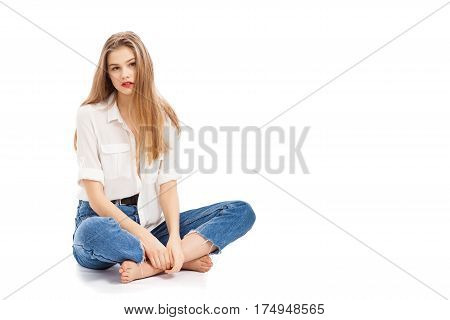 Cute girl in jeans sits on a white background