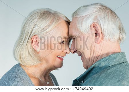 side view of smiling senior man and woman looking at each other on grey