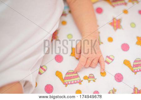 hand of a sleeping newborn baby lying a baby blanket