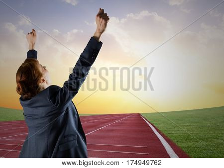 Digital composite image of a businesswoman winning the race on race track