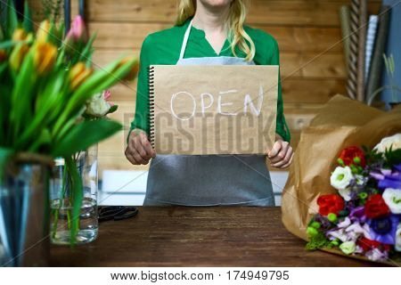 Owner of flower-shop showing note 'open'