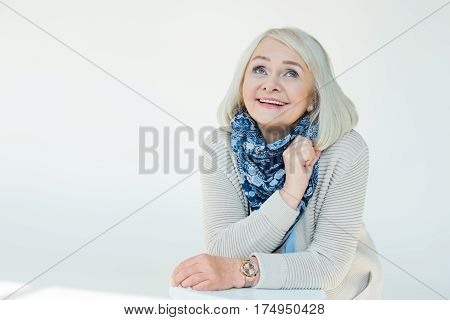 portrait of dreamy senior woman on white poster