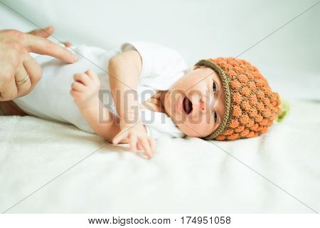 cute newborn baby in knitted hat lying on the bed