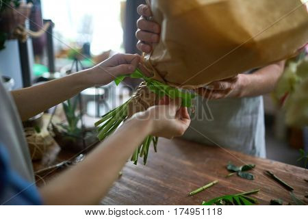 Human tying arranged bouquet with green ribbon