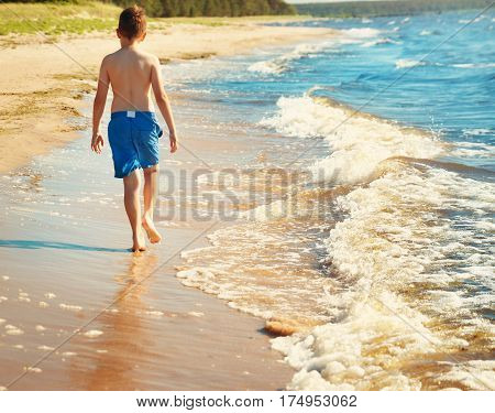 boy barefoot is jumping on the beach in water. Child is on vacation in summer at the sea