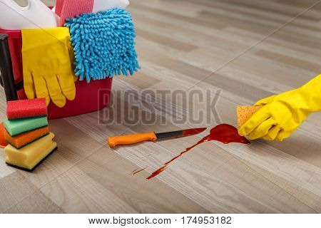 Crime cleaner concept. Bucket with sponges, chemicals bottles and plunger. Hand in rubber glove holding a sponge. Paper towel. Knife and splash of blood.