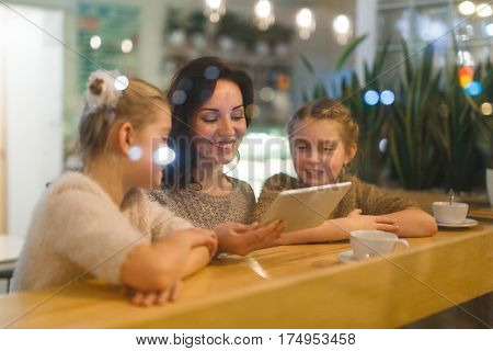Affectionate mother and daughters browsing in the net in cafe