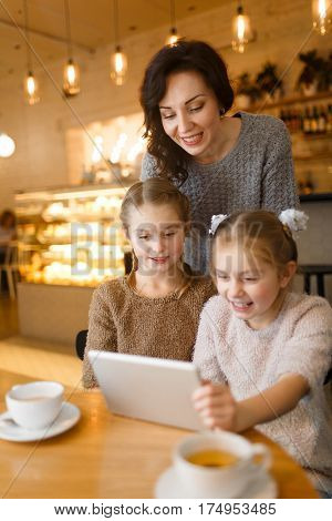 Modern young woman and her twin daughters with touchpad spending leisure in cafe