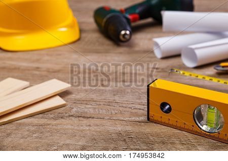 Helmet, screwdriver and tape measure. Paper plans and knife. Wooden planks and building level.