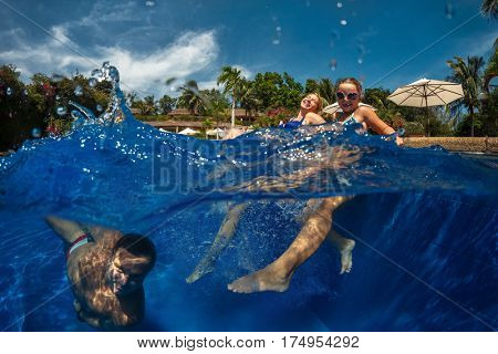 Pretty little girl with her parents in swimming pool.