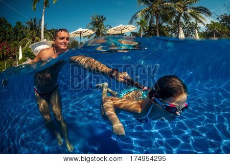 Happy active family young father and his cute daughter adorable toddler girl playing in a swimming enjoying summer vacation