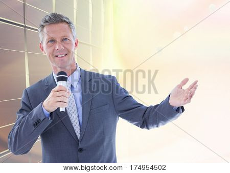 Portrait of businessman public speaking on microphone against bright sunlight