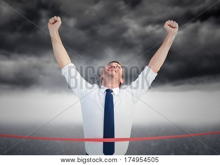 Digital composite image of excited businessman crossing the finish line against storm clouds