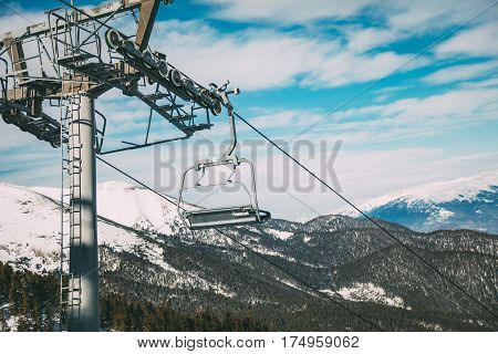 Ropeway and chair lifts driving at ski resort on beautiful snowing day. Landscape.