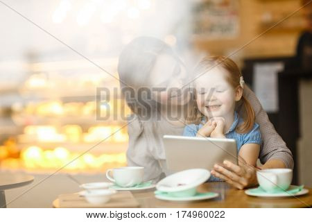Woman showing her daughter interesting cartoon in touchpad while sitting in cafe