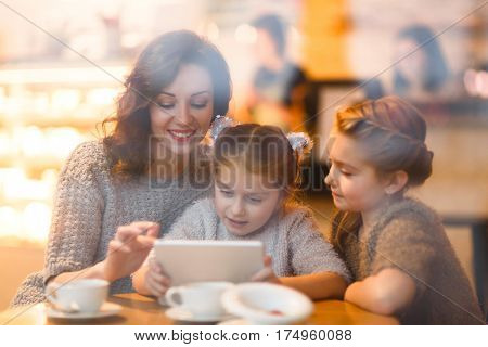 Twin sisters and their mother with touchpad sitting in cafe