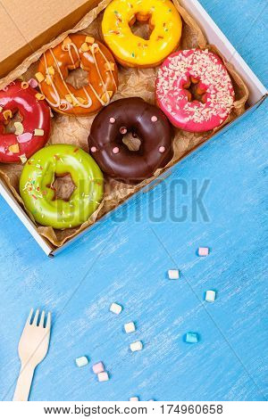 Donuts with icing. Sweet glazed donut. Dessert in delivery box. Wooden fork with colored marshmallows. On blue background.
