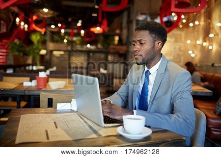 Portrait of confident African American man wearing business suit busy working with laptop at table in cafe, looking at computer screen