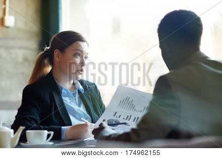 Two business people during work meeting in modern cafe: Young professional woman explaining statistics data holding documents with graphs to male partner