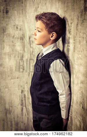 Portrait of a sad boy. Seven year old boy in elegant school clothes standing by a grey wall with a sad face. Loneliness.