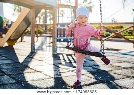 Cute little girl trying to sit on a seesaw. Horizontal outdoors shot.