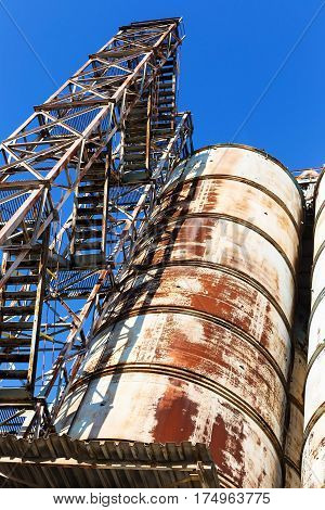 Old, Abandoned Concrete Plant With Iron Rusty Tanks And Metal Structures. The Crisis, The Fall Of Th