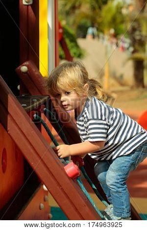 Cute baby boy with blond hair ponytail in blue tshirt and jeans climbing rope net or ladder on sunny summer day on playground background