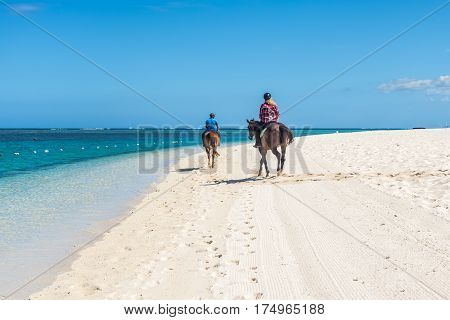 Le Morne Mauritius - December 11 2015: Couple riding on horseback along the sea on the Le Morne Beach one of the finest beaches in Mauritius and the site of many tourism facilities.