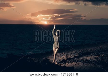 Pretty girl or beautiful woman with long brunette hair wearing sexi brown shirt standing on rocky shore at dark blue sea or ocean during idyllic sunset under cloudy sky on rosy sky background