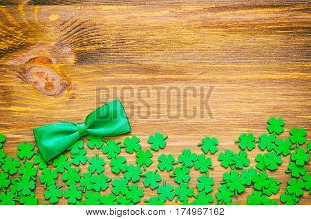 St Patrick Day background - green quatrefoils and bow tie on the wooden background. St Patrick Day festive background with free space for text. Concept of St Patrick Day holiday. St Patrick Day is national Irish holiday