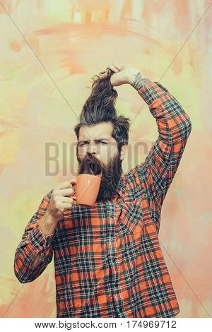 Angry bearded man caucasian hipster with long beard and moustache holding stylish fringe hair haircut and orange cup in red plaid shirt on abstract pink wall background