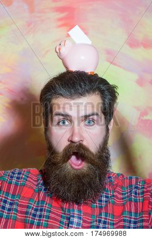 Surprised bearded man caucasian hipster with long beard and moustache in red plaid shirt with pink ceramic piggy bank and banknote on head on abstract colorful wall background. Saving money concept