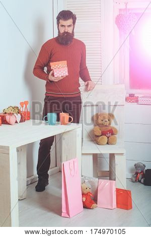 Bearded man caucasian hipster with long beard and moustache in brown sweater with gift boxes standing at table with cups hearts teddy bears on chair floor for valentines day on white wall