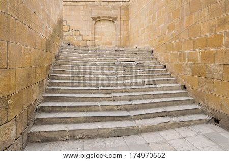 Ancient wide stone staircase framed by stone walls from three sides