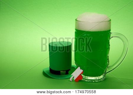 St Patrick's Day green beer with shamrock and Leprechaun hat on green background.